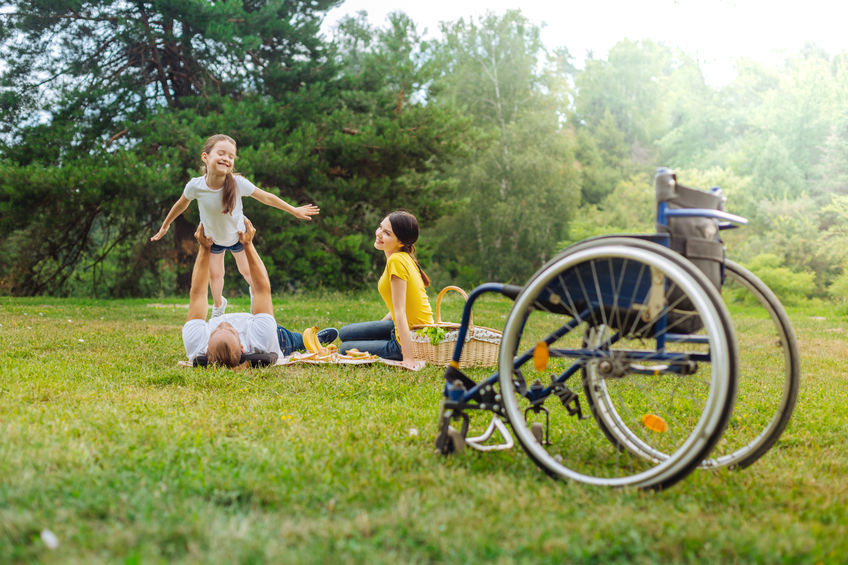 Joyful girl playing with her disabled dad lying on grass